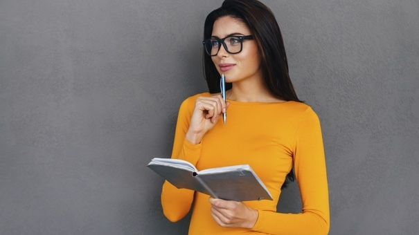 Waiting for inspiration. Thoughtful young and beautiful woman touching chin with pen and holding notebook while standing against grey background